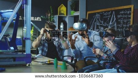 Black man with group of kids having lesson about 3d modeling wearing VR glasses in lab. #1036687360