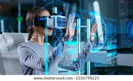 In Laboratory Scientist Wearing Virtual Reality Headset Sitting in a Chair Interacts with Futuristic Holografic Interface, Showing Neurological Data. Modern Brain Study/ Neurological Research Center. #1036798225