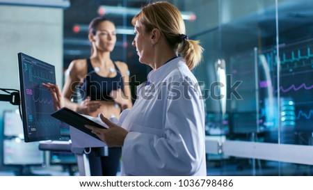 Sport Scientist Supervises Touches Display Showing EKG Status While in the Background Woman Athlete Running on a Treadmill with Electrodes Attached to His Body. Laboratory with High-Tech Equipment. #1036798486