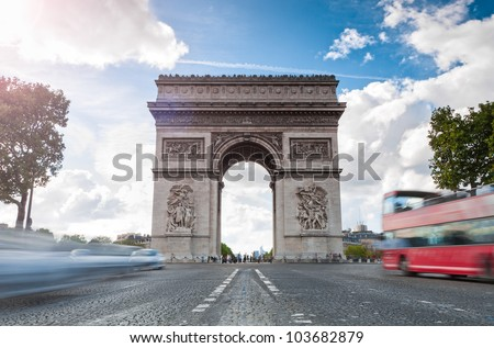 Triumphal arch. Blue sky and white clouds in background. Blurred cars and red tourist bus in foreground. Paris, France, Europe. #103682879