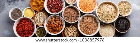 Superfoods and cereals selection in bowls: quinoa, chia, goji berry, mung bean, buckwheat, bean, turmeric, polba, bulgur, lentil, sesame, flax seed, wild rice, almond on grey concrete background #1036857976