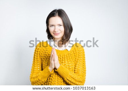 beautiful young woman in prayer, isolated on gray background #1037013163