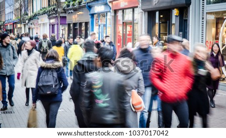 Motion blurred crowd of shopping walking on busy fashion shop street  #1037017042