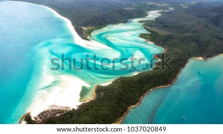 A beautiful aerial view of turquoise waters, white sandy beaches and green forests in the paradise of the Whitsunday's islands, Australia. Concept for summer, holidays and travelling #1037020849