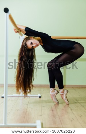 Young beautiful dancer posing in studio wit Ballet bar on tiptoe. Modern sexy brunette girl wears black tights practiced with handrail in the dance Long amazing hair. #1037025223