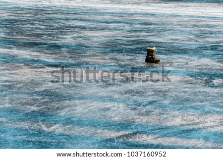 Close-up of the ice surface of the pond. There are cracks in the ice, a shoe that has been forgotten on the ice. Beautiful blue texture. #1037160952