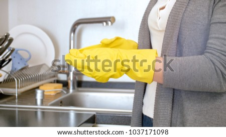 Closeup photo of woman taking off yellow latex gloves #1037171098