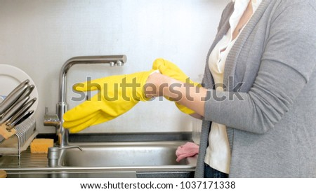 Closeup image of woman wearing yellow protective gloves #1037171338