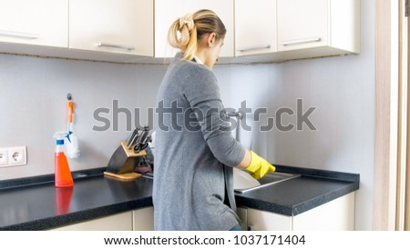 Rear view image of young housewife washing dishes in kitchen sink #1037171404