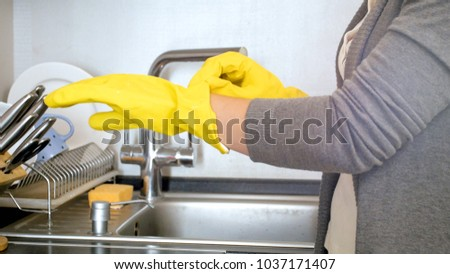 Closeup image of young woman in latex gloves on kitchen #1037171407
