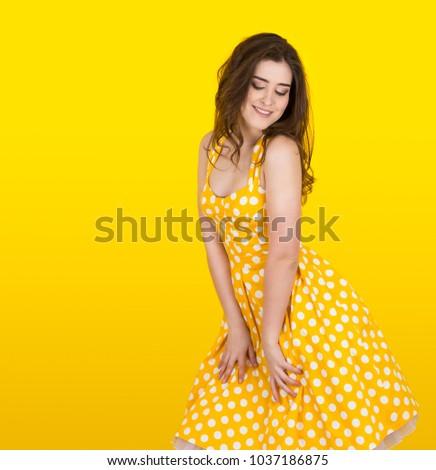 A girl in yellow polka-dress is posing like Marilyn Monroe