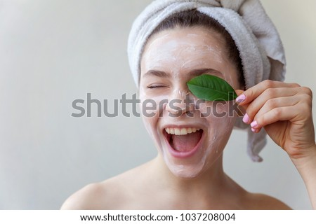 Beauty portrait of a smiling brunette woman in a towel on the head with white nourishing mask or creme on face and green leaf in hand on white background isolated. Skincare cleansing eco organic #1037208004