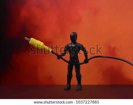 USB cable. USB cable, in the hands of Superman. Red background. USB cable on a red background. Plastic man