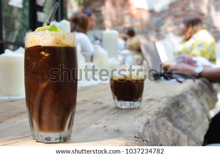 The espresso coffee with ice cube  drink to enjoy hot weather of the summer with the background of cafe with old brick wall. #1037234782