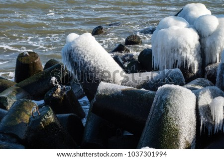 Baltic Sea in Poland. Entrance to the port, ice-covered concrete breakwater. Season winter. #1037301994