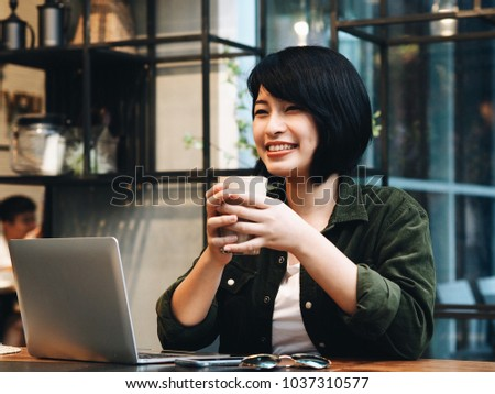 Young Asian woman drinking coffee and using laptop in coffee shop. #1037310577