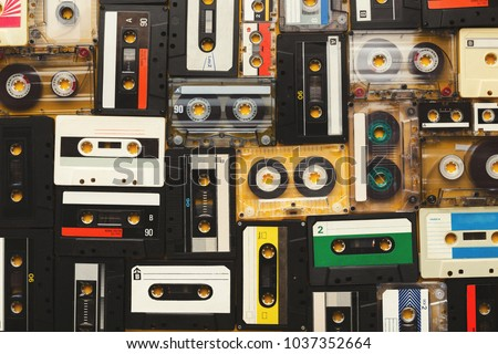 Retro audio cassette tapes on beige background. Top view on vintage media devices, copy space on labels, flat lay #1037352664