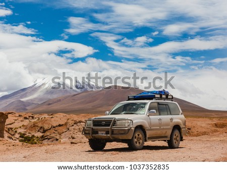 Eduardo Avaroa National Park, Bolivia, February 2018: offroad vehicle driving in the wilderness of Andean mountains covered in snow  #1037352835