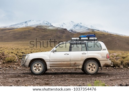 Eduardo Avaroa National Park, Bolivia, February 2018: offroad vehicle driving in the wilderness of Andean mountains covered in snow  #1037354476