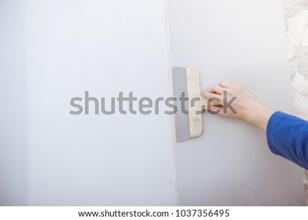 young man doing repairs in apartment, wallpapering on wall #1037356495