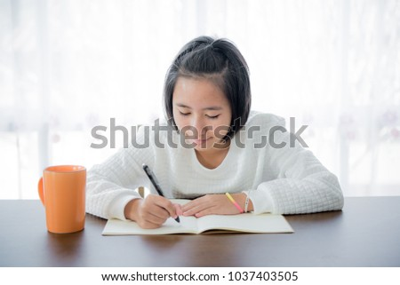 The girl is writing on the table in the room with the light from the back. #1037403505