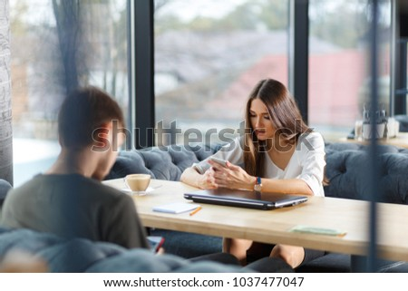 always connected, internet addiction, young people in cafe looking at their smartphones, social network concept #1037477047