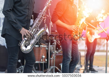 World Jazz festival. Saxophone, music instrument played by saxophonist player and band musicians on stage in fest. #1037503036