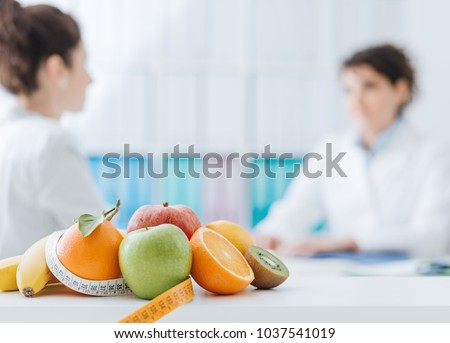 Professional nutritionist meeting a patient in the office and healthy fruits with tape measure on the foreground: healthy eating and diet concept #1037541019