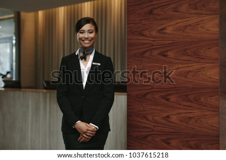 Portrait of happy female hotel receptionist standing at workplace. Smiling woman receptionist working in hotel. #1037615218