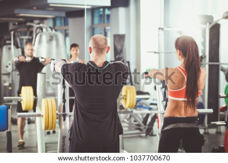 Beautiful woman at the gym exercising with her trainer . Beautiful woman. #1037700670
