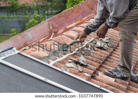 Asian worker secure and patch roof tiles with cement on old building roof #1037747890
