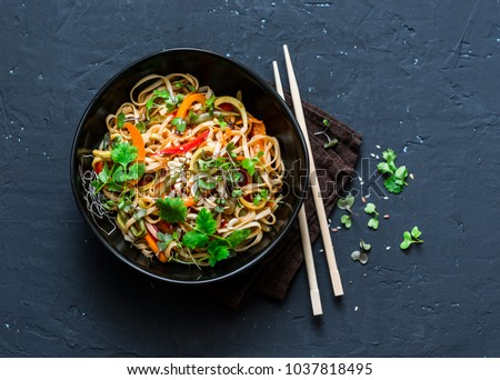 Pad Thai vegetarian vegetables udon noodles in a dark background, top view. Vegetarian food in asian style. Copy space  #1037818495