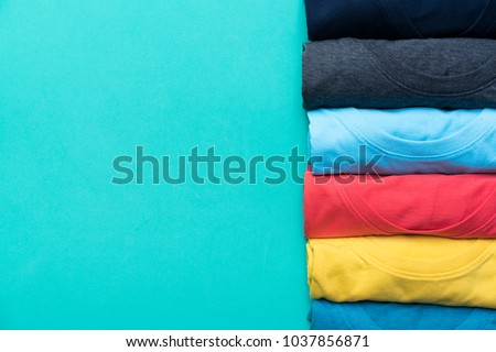 close up of rolled colorful clothes on green background #1037856871