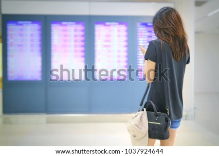 Back side of asian female passenger looking at departure display and check flight on mobile phone at the airport. Soft focus with blurred background. Transportation, people and technology concept.   #1037924644