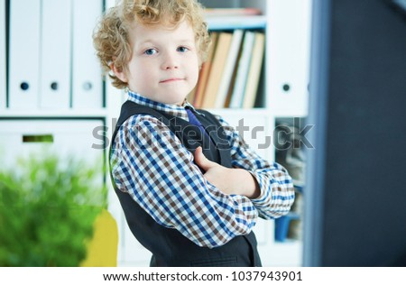 Little Caucasian curly boy presents himself as a businessman posing near the desktop with a monitor in the office #1037943901