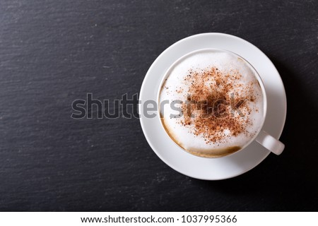 Cup of cappuccino coffee on dark table, top view #1037995366