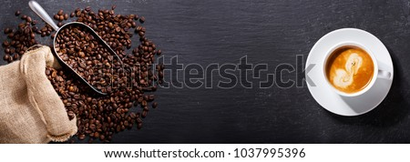 cup of coffee and coffee beans in a sack on dark background, top view #1037995396