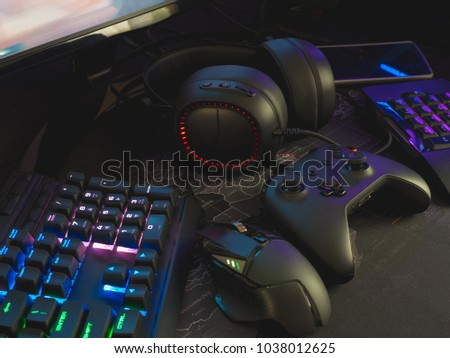 Gamer workspace concept with gaming gear, mouse, keyboard, joystick, Headset and mouse mat on table background with RGB Color.