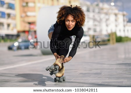 Young fit black woman on roller skates riding outdoors on urban street. Smiling girl with afro hairstyle rollerblading on sunny day