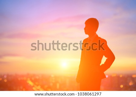 silhouette of business man look somewhere with sunset #1038061297