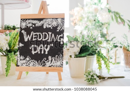 Hand writing of white wedding day word on wooden frame blackboard with small flower houseplants placed to decorate on table for valentine or love concept