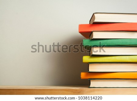 Stack of colorful books on wooden desk. Copy space for text. Back to school. Education background #1038114220