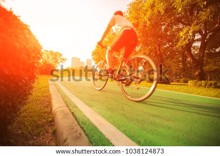 A woman is cycling into the sunset in the park. #1038124873