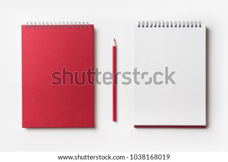Design concept - Top view of red spiral notebook and color pencil collection isolated on white background for mockup #1038168019