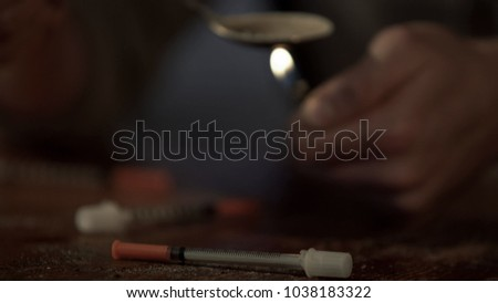 Closeup of syringes and male drug addicts hands preparing heroin dose for shoot #1038183322