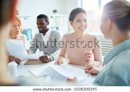 Happy young manager or accountant looking at her colleague with smile during conversation #1038200395
