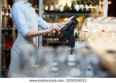Close-up of waitress registrating orders at the cash desk Royalty-Free Stock Photo #1038204025