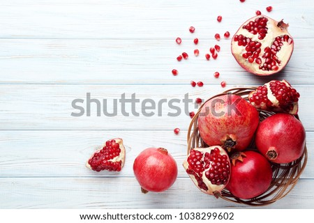 Ripe and juicy pomegranate in basket on wooden table #1038299602