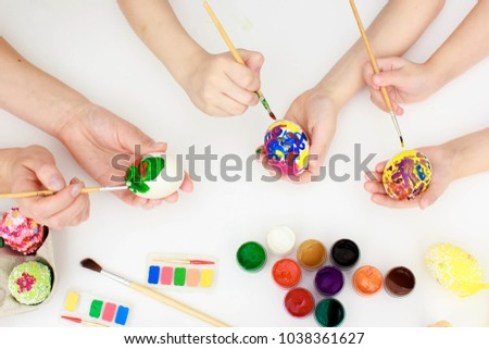 Easter holiday,happy hamily - a mother and her daughters -painting Easter eggs. Happy family preparing for Easter. Happy easter #1038361627