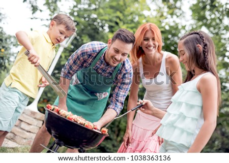 Dad teaches kids to make barbecue in the backyard,everyone is having fun.Leisure,food,people and holidays concept. #1038363136